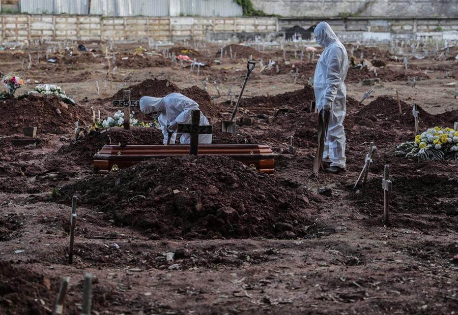 Empleados de una funeraria realizan el entierro de una persona que falleció a causa de la COVID-19 en el cementerio de Caju.